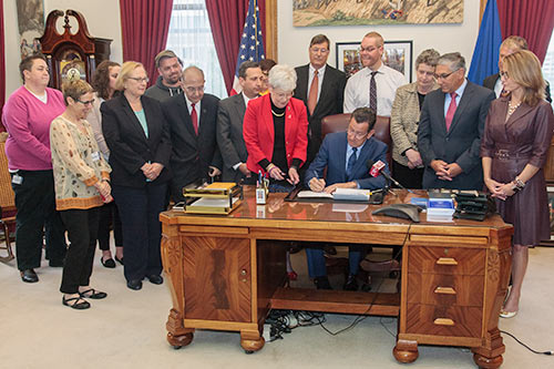 Photo of Governor Malloy signing the conversion therapy bill.